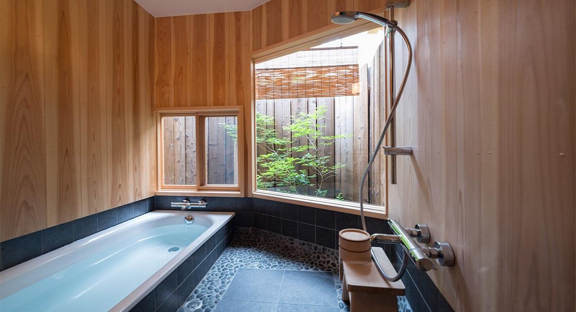 大きな窓で坪庭を望む浴室。