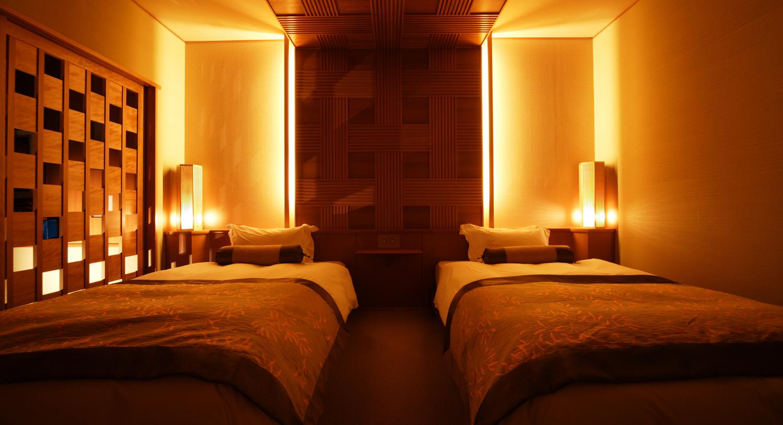 【客室内ベッドルーム】落ち着きのある設え。ベッドはシモンズ社のマットレスを使用