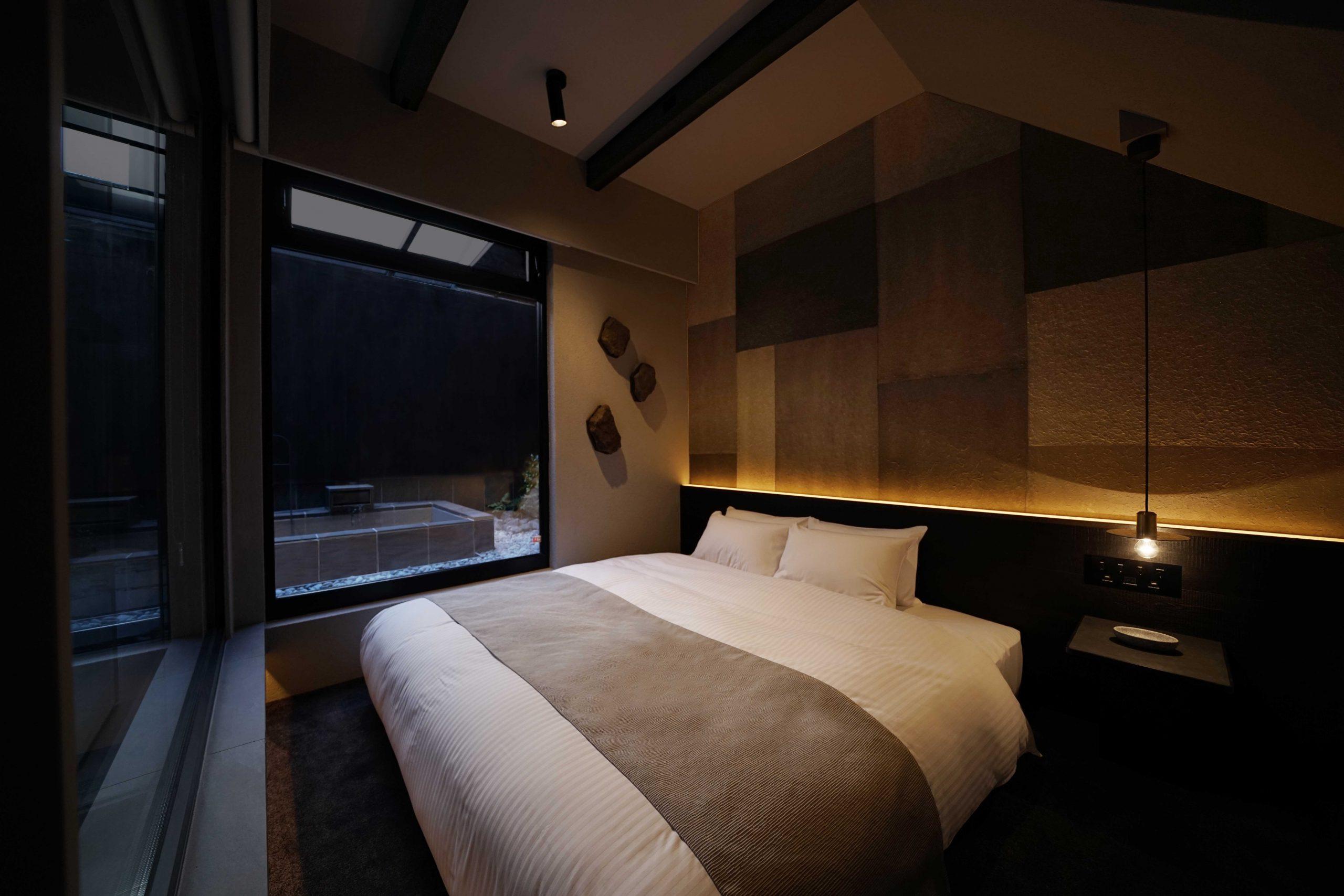 デラックスタイプ客室「IWA」ベッドルームからガラス越しに見える空間には半露天風呂がある。