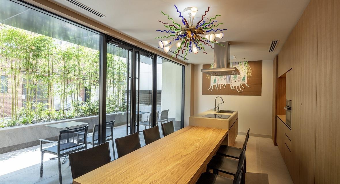 テラスに面したゲストキッチンは、アイランドキッチンとダイニングテーブルを備えた、グループや家族単位で使用することができるパーティ用キッチンスペース。