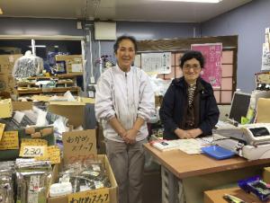 店頭の千葉ひろ子さん(右)と公子さん(右) 後ろには3月26日に南三陸仮設住宅近隣のホールで実施した「上野千鶴子さんを囲む会」のポスターも見えます。
