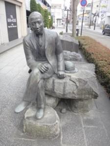 材木町商店街には宮澤賢治さんが座って歓迎しています
