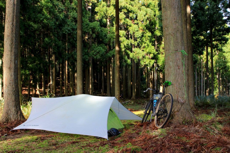 林間キャンプ場で一夜を過ごすための準備。木々が多い場所はタープが張りやすく、また風や雨を凌いでくれるのでお気に入りの場所です。ただし地面からの結露がすごいのでグラウンドシートは必須です。photo:神楽坂つむり