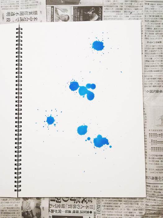 ドリッピングの過程。筆に絵の具をつけ、紙の上から垂らす