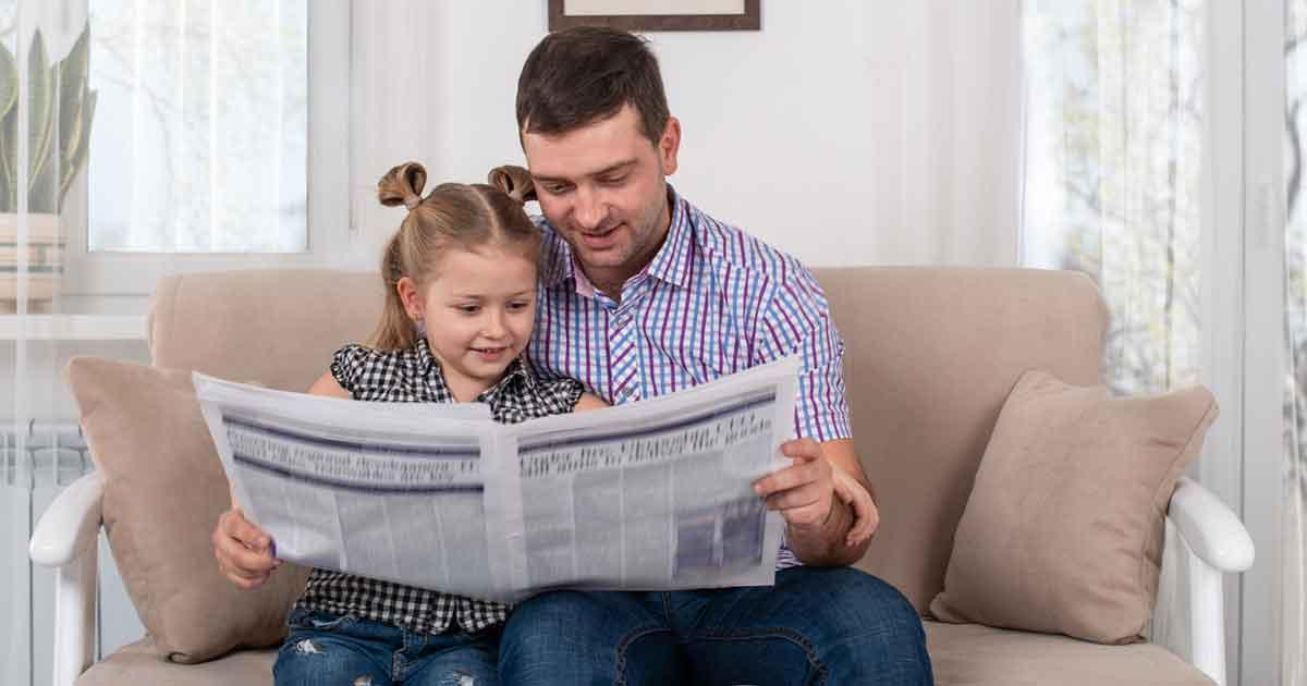 ソファーで新聞を読む子どもと父親