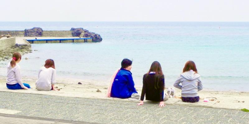 浜辺に座っている人達