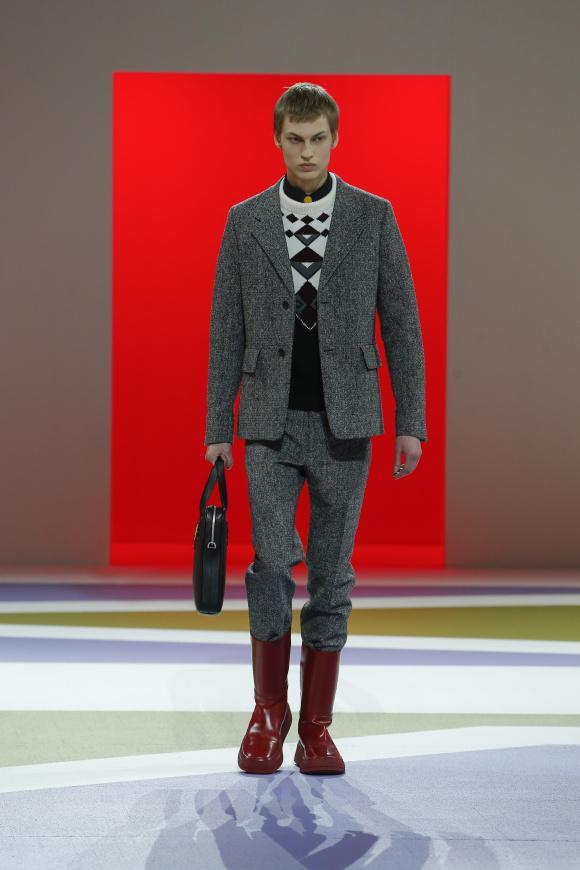 色あざやかなブーツを合わせた、 古典的なツイードスーツ