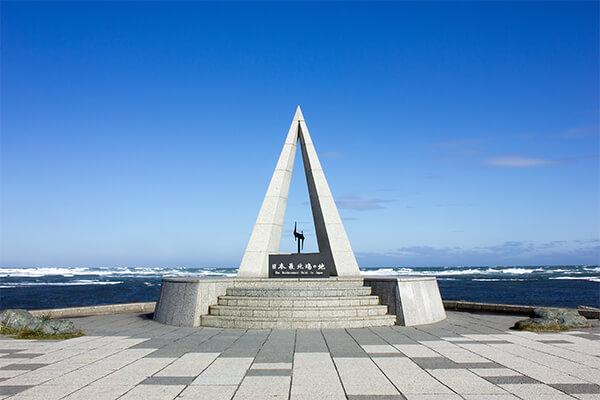 日本最北端の地、北海道稚内市(わっかないし)。稚内市の宗谷岬には、北緯45度31分22秒の日本最北端の地を示す記念碑が建てられています。北極星を指すように伸びる鋭角に空へ伸びたモニュメントの中央には北を示すN、台座は「平和と協調」を表し円形となっています。 この宗谷岬には、大晦日に最北の初日の出を見るため、日本中から多くの人が集まります。観光客向けに1988年から始まったのが、「初日の出inてっぺん」というイベント。花火やかがり火の点火が行われた後、先着1000名に新年の干支のキーホルダーが配られ、全種類を集めようと毎年訪れる人がいるほど人気を集めています。 その宗谷岬の裏手には、北海道遺産「宗谷丘陵(そうやきゅうりょう)」が広がっています。57基の風力発電施設があり、道にホタテの貝殻を敷き詰めて作られた「最北の白い道」はみどころです。 もちろん稚内駅の近隣にも自然を楽しめるスポットがあります。駅から車で30分ほどの「道立宗谷ふれあい公園」は、大沼の北岸にあるオートキャンプ、パークゴルフが楽しめる施設。大沼に飛来する水鳥を観察できる「大沼バードハウス」、アヒルやうさぎ、ヤギが見られる「動物ふれあいランド」なども人気のスポットです。稚内空港園内にある「メグマ沼」は5月から8月下旬にかけて200種以上の草花とバードウォッチングに適しています。「宗谷ふれあい公園」から車で5分ほどの場所に、それぞれのスポットが集まり観光に便利。 また利尻島、礼文島、サハリンなど島影に沈む夕日は、最北端稚内でしか見ることのできない美しい景色です。