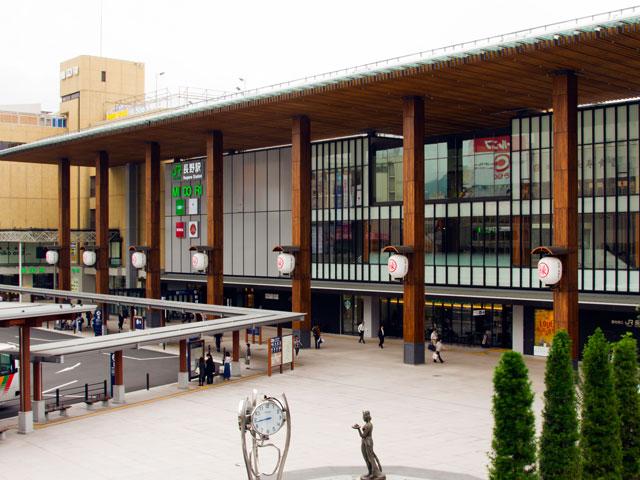 長野県の県庁所在地・長野市にある長野駅は、県内でも最大規模のターミナル駅です。北陸新幹線のほか、在来線のJR信越本線、しなの鉄道北しなの線、長野鉄道長野線が乗り入れています。東京駅から新幹線で約1時間半。信州まつもと空港(松本空港)から高速道路を利用すれば、約1時間15分で到着します。 2015年、北陸新幹線の金沢延伸にともない、駅舎の善光寺口側は、地元の杉材を使った大柱がそびえる「門前回廊」へとリニューアルしました。駅ビルのMIDORI二階は、おやきや野沢菜、りんごのスイーツなど信州の特産品、名産品を取り扱う「信州おみやげ参道」です。 年間600万人の観光客が訪れる善光寺は、善光寺口から車でおよそ15分。江戸時代から「一生に一度は善光寺詣り」と語り継がれてきた長野観光の定番スポットです。日本最古の仏像といわれる善光寺のご本尊、一光三尊阿弥陀如来を安置する本堂は、国宝にも指定されています。駅から善光寺まで続く中央通り(県道32号線)は表参道にあたり、カフェやお土産店、信州そばのお店を巡る散策が楽しめます。 戦国時代に武田軍と上杉軍が戦った川中島古戦場史跡公園は、駅東口から上越信濃自動車道の長野IC方面に向かい、車でおよそ20分。1998年に行われた長野冬季オリンピックでスピードスケート競技会場として使われたエムウェーブ(長野市オリンピック記念アリーナ)は、東口から県道58号線経由で約15分です。最寄りインターの長野ICは、駅から約20分で到着します。