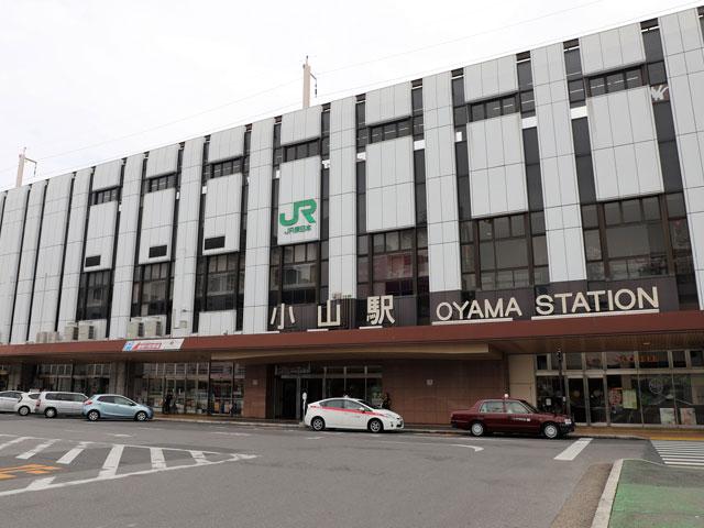 JR小山駅は、東北新幹線と在来線の宇都宮線、両毛線、水戸線が乗り入れる栃木県小山市の鉄道駅です。東北新幹線の「なすの」や「やまびこ」に乗れば、東京駅から約45分で到着します。湘南新宿ラインや上野東京ラインとの直通運転もあり、新宿駅や横浜駅、熱海駅から乗り換えなしでアクセスできます。 小山駅の周辺は北関東の幹線道路となる国道4号線と国道50号線が走り、車のアクセスも快適です。国道4号線と国道50号線が交わる神鳥谷(ひととのや)交差点は駅西口から2km、車でおよそ7分で到着します。東口駅前のロータリーにそびえる建物は、白鴎大学の東キャンパスです。 CMソングでおなじみだった小山ゆうえんち跡地は、大型ショッピングセンター「おやまゆうえんハーヴェストウォーク」としてリニューアルしました。小山駅から国道4号線経由でおよそ10分。週末には渋滞も起こる人気施設です。佐野市の佐野プレミアムアウトレットも、駅から国道50号線を経由しておよそ40分で到着します。 小山駅の周辺は、かつて日光街道の宿場町として栄え、徳川家康が関ケ原の戦いで勝利をつかむきっかけとなった「小山評定」の行われた地としても有名です。現在の小山市役所は、小山評定が行われた跡地に建てられています。平安時代に藤原秀郷の創建と伝わる初詣の定番スポット・須賀神社も、市役所から徒歩圏内です。 小山駅の西口からおよそ1km、思川(おもいがわ)の河川敷は、小山市原産の桜「思川桜」が薄紅色の花を咲かせるお花見スポット。毎年7月下旬に開催される花火大会「おやまサマーフェスティバル」では打ち上げ会場となり、当日は周辺道路の交通規制も行われます。東北道の宇都宮ICや矢板IC、水戸、大洗方面の北関道・桜川筑西ICはそれぞれ駅から約1時間です。