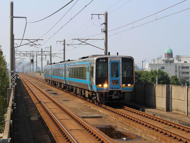 丸亀駅は香川県の瀬戸内海側の丸亀市新町にある、白い壁の色が印象的な高架駅です。JR予讃線が乗り入れており、県内の高松駅あるいは愛媛県の松山駅方面への移動が可能です。構内には、コンビニ、イートインのあるベーカリー、スーパーやカフェなどがあります。 南口へ出ると、各路線バスの停留所が並んでいます。市内を移動するためのコミュニティバス、空港間を往復するリムジンバス、大阪・名古屋・新宿・福岡方面へと運行する高速バスなどが発着しています。 丸亀駅南口を出て西へ向かうと特色のある建物があることに気づくでしょう。丸亀市にゆかりがある画家、猪熊弦一郎氏本人から寄贈された作品が並ぶ、「猪熊弦一郎現代美術館」です。MIMOCA(ミモカ)という名称で親しまれ、開かれた駅前美術館として多くの来場者が訪れています。さらに南下すると石垣の名城としても知られる丸亀城があり、季節ごとのイベントも開催されています。 また、駅から北へ徒歩で約5分、車でなら数分の所には丸亀港があり、フェリーを利用でき、金比羅宮へ続くこんぴら街道の起点「太助灯籠」、丸亀の特産品であるうちわの博物館「うちわの港博物館」へと脚を伸ばすこともできます。各スポット周辺には駐車場が用意されており、ドライブを楽しみながら名所を廻ることができるでしょう。 高松空港からは高松自動車道を利用すると45分ほど、高松自動車道坂出I.C.または善通寺I.C.からは約20分で丸亀駅にアクセスできます。