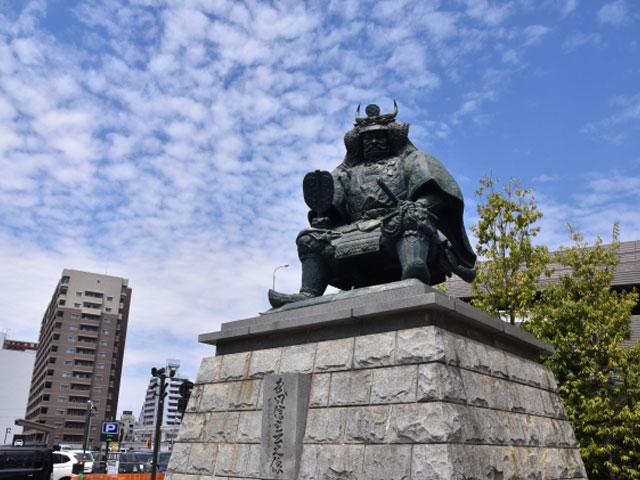 新宿駅から電車を利用して約1時間30分。甲府駅は、戦国時代の名武将・武田信玄ゆかりの地、山梨県の玄関口です。首都圏から長野県・塩尻駅を経由し、愛知県名古屋市へと延びるJR東日本・中央本線が乗り入れ、静岡県富士市と甲府市を結ぶJR東海・身延(みのぶ)線に接続しています。 駅の周りには、駅ビルセレオ甲府や山交百貨店などの商業施設、県庁や県立科学館、図書館などの行政・公共施設が集結し、甲府市の中心市街地を形成しています。南口にどっしりかまえた信玄像は、フォトスポットとして人気です。駅から歩いておよそ5分の場所には、江戸時代に西の備えとして活躍した甲府城(舞鶴城)の遺構を利用して整備された舞鶴公園もあります。 武田氏の本拠地として有名な躑躅ヶ崎館(つつじがさきやかた)、現・武田神社へは、北口に面する武田通り(県道31号線)を直進して約7分でアクセスできます。信玄公生誕の城として知られ、国の史跡にも指定されている要害山城へは、武田神社から県道31号線をさらに北上して約10分です。駅からおよそ30分圏内には、信玄の隠し湯としても知られる湯村温泉や積翠寺温泉、国の特別名勝「昇仙峡(しょうせんきょう)」もあります。 甲府市内では、例年4月12日の信玄公の命日に合わせて、甲冑姿の武者行列が街中を練り歩く「武田二十四騎馬行列」や「信玄公祭り」などのイベントも開催されています。信玄公祭りでは、駅南口一帯に交通規制が敷かれますので、お出かけ前に道路情報を確認しておきましょう。