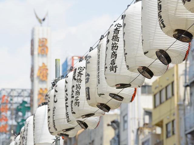 大阪府大阪市にある心斎橋駅は、御堂筋線と長堀鶴見緑地線が乗り入れています。また、改札内で四ツ橋駅に連絡しています。御堂筋線の中では6番目に乗降人数が多く、長堀鶴見緑地線の中では1番多いです。また、第1回近畿の駅百選に選ばれています。 もともと心斎橋は、長堀川に架かっていた橋の名前でした。現在は、長堀川は埋め立てられ心斎橋も撤去されていますが、クリスタ長堀の天井部を川に見立て、長堀川の水面を再現しています。 御堂筋線地下道直結の大丸心斎橋店は、重厚感のある外観で高級ブランドや飲食店、食品まで厳選されたショップが並び観光客で賑わいます。地下二階の食品フロアでは、大阪土産を購入することもできます。心斎橋商店街を進むと、大阪の観光地の一つである「アメリカ村」があります。通称アメ村と呼ばれ、古着店や飲食店が建ち並びます。大阪名物のたこやきをはじめ食べ歩きグルメを楽しむのがおすすめ。 車では国道25号線を経由し5分ほどで「道頓堀橋」につきます。道頓堀橋には、グリコの看板や、かに道楽などがあり、観光スポットが多くあります。また、道頓堀川にはミニクルーズがあり、川から街の様子を見ることができます。 車で府道30号線と国道308号線を経由すると、17分ほどで大阪城に到着します。大阪城は、8階建てで豊臣秀吉についての展示物があり、最上階は展望室となっています。大阪のまちを一望できるので、幅広い年代で楽しめます。大阪城は見るだけではなく、試着体験ができます。復元した戦国武将の兜がかぶれたり、女性用の小袖も用意してあり写真撮影もできます。