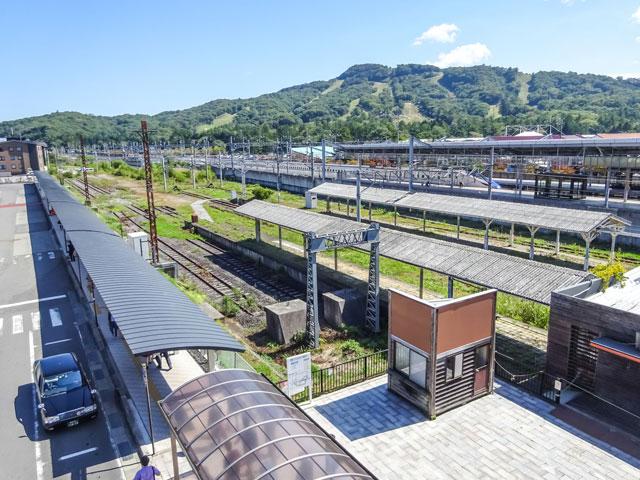 軽井沢駅は、長野県の高原リゾート・軽井沢の玄関口です。関東地方と北陸地方を結ぶ北陸新幹線と、観光列車・ろくもんも運行するしなの鉄道が乗り入れています。新幹線を利用すれば東京駅から70分、長野駅から30分でアクセスできます。 しなの鉄道の駅舎は、2017年に「旧駅舎口ゾーン」として新たに生まれ変わりました。明治時代に使われていた軽井沢駅の旧駅舎を模した建物には、信州銘菓の栗菓子を提供するカフェに特産品のハムや味噌を扱うお土産店、ミニSLやレールバイクなどの子ども用遊具が併設されており、新たな駅ナカ施設として注目されています。 駅の南口前には、国内最大級のアウトレットモール「軽井沢・プリンスショッピングプラザ」が広がっています。国内外の有名ブランド店を中心に、230以上のショップが集まった人気のお買い物スポットです。駅の反対口(北口)から車で6分の場所には、100年以上の歴史をもつジャム店や名物のモカソフトクリームを扱うカフェなど、200以上のお店が並ぶ「旧軽井沢メインストリート(旧軽井沢銀座商店街)」もあります。 湖上のバラ園が整備された軽井沢レイクガーデンや、緑豊かな敷地内に絵本の森美術館やおもちゃ博物館が集まるムーゼの森は、駅南口からそれぞれ車で約20分。駅の西側、中軽井沢駅方面には、ハイキングも楽しめる標高1,256mの離山(はなれやま)もあります。 駅の最寄りICは、長野県と新潟県を結ぶ上信越自動車道の碓氷軽井沢ICです。駅からは約15分で到着します。