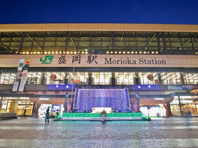 盛岡駅は、岩手県の県庁所在地・盛岡市のアクセス拠点です。東北・北海道新幹線と秋田新幹線が乗り入れ、東京駅から最速約2時間10分、仙台駅から約40分。在来線はJR東日本の田沢湖線、東北本線、山田線と、IGRいわて銀河鉄道線が停車します。 南部鉄器や南部せんべい、わんこそばなど数々の特産品や名物グルメで知られる盛岡市は、岩手県の中心部にある中核市です。駅周辺に広がる市街中心部には、明治から大正時代に建てられたレトロな町並みが今も残り、盛岡で青春時代を過ごした宮沢賢治や石川啄木ゆかりのスポットも点在しています。 かつて盛岡藩の城下町で中心となった盛岡城の跡地に整備された盛岡城跡公園(岩手公園)や、周囲21mの巨石を割って咲く「石割桜」は、駅から車でおよそ10分。岩手県庁のそばにあります。県庁前から市内を流れる中津川を渡れば、明治時代の銀行建築物を活用したもりおか啄木・賢治青春館や岩手銀行赤レンガ館に到着します。県庁や市役所、赤レンガ館の建つ中央通りや中ノ橋通りは、毎年8月1日~4日にかけて行われる「盛岡さんさ踊り」のパレードや輪踊りの会場です。沿道には、本場盛岡の冷麺やわんこそば、じゃじゃ麺が楽しめるグルメスポットも充実しています。 盛岡市街から最寄りインターチェンジの東北自動車道盛岡ICは、国道46号線経由でおよそ7km。いわて花巻空港からレンタカーで盛岡市街に向かう場合は、東北自動車道を経由して約40分で到着します。