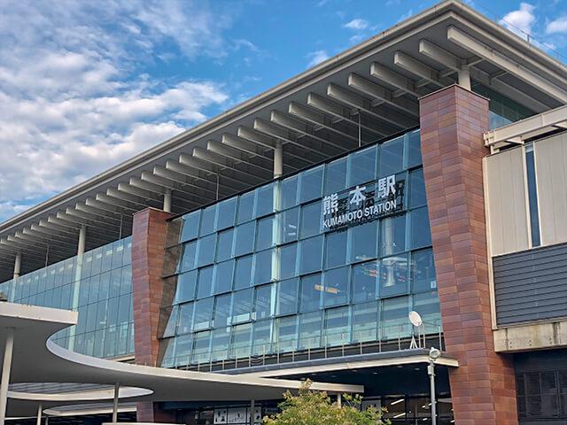 JR熊本駅は、福岡から鹿児島までの九州全土を繋ぐ九州新幹線と鹿児島本線、大分県まで伸びる豊肥本線(通称:阿蘇高原線)が乗り入れ、熊本市内をめぐる熊本市電への乗り換えも便利なアクセス拠点です。土日やGW、夏休みなど長期休暇には、特急「あそぼーい!」や「A列車」、蒸気機関車が牽引する「SL人吉」とJR九州の人気観光列車も運行しています。 駅高架下の「肥後よかもん市場」は、熊本を代表するお土産が揃うショッピングスポットです。人気の銘菓「武者返し」や「黒糖ドーナツ棒」、うにからすみや馬刺しも駅チカですぐに揃います。 市内の主要観光スポットは駅から若干離れているため、熊本観光のお出かけは、レンタカーが便利です。築城の名手・加藤清正公が築いた熊本城は、駅から車で約13分。細川氏ゆかりの名勝「水前寺成就園」は、約20分で到着します。 熊本市街から阿蘇山まで続く県道111号線、通称「阿蘇パノラマライン」は、高原を走る絶景ドライブコース。道中は健康テーマパークの「阿蘇ファームランド」や、阿蘇火山博物館などタイよりスポットもいっぱいです。火口が見学できる阿蘇山頂までは、天候によって入山規制が敷かれることもあります。お出かけ前には、阿蘇市ホームページから阿蘇火山加工規制情報をチェックしておきましょう。