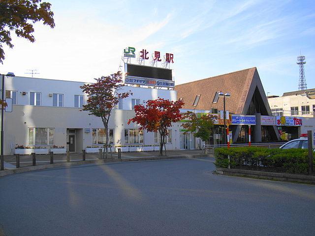 北見駅は、北海道北見市にある北海道旅客鉄道(JR北海道)・日本貨物鉄道(JR貨物)石北本線の駅です。北見市の代表駅であり、特別快速「きたみ」の始発・終着駅です。また、特急「オホーツク」・「大雪」を含めた全ての列車が停車する駅でもあります。駅舎内にはみどりの窓口やキヨスク、駅レンタカー事務所などがあり、以前は駅弁の販売や立ち食い蕎麦屋もありましたが、今では閉店してしまいました。 北見駅の周辺は北見市の中心市街地となっていて、野付牛公園、東陵公園へは車で約10分。北見ハッカ記念館・薄荷蒸溜館へは車で約5分のアクセスです。 駅を出て左手には、隣接するまちきた大通ビル(パラボ)があり、その一階には北見バスターミナルが設置されています。北見市内線「大通」、郊外線「北見」、都市間バス「北見バスターミナル」がこのバスターミナルに該当し、最寄りの空港である女満別空港まではここからバスで45分の位置にあります。 北見市には温根湯温泉やキタキツネ牧場、1m級のイトウを多数飼育する山の水族館などがあります。また、有名な「北見ハッカ」に関する資料館である北見ハッカ記念館は、北見駅から徒歩10分の距離にあります。