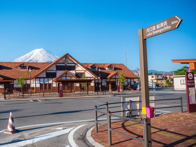 富士急行河口湖線が乗り入れる河口湖駅は、山梨県の富士山や富士五湖めぐりの拠点となる駅です。富士山を背景に美しく映える木造の駅舎は、「関東の駅百選」に選ばれました。 駅構内にはお土産屋さんや観光案内所、飲食コーナーが充実しています。富士山観光に訪れる訪日外国人観光客でも賑わい、外貨の自動両替機も構内に設置されています。 河口湖は駅のすぐ目の前です。駅前から御坂みち(国道137号)を北向けに進むと、遊覧船やカチカチ山ロープウェイの乗り場がある湖岸にたどりつきます。さらに湖岸を北へ進んだ先が、湖越しに富士山を望むドライブコース、湖北ビューライン(県道21号)です。 河口湖西岸から湖北ビューラインを西に進むと、富士五湖の西湖(さいこ)、精進湖(しょうじんこ)、本栖湖(もとすこ)へアクセスできます。河口湖駅から本栖湖までは、約25kmの道のりです。沿道には郷土料理のほうとうが味わえるお店も点在し、ドライブ中のお食事処にも困りません。 富士五湖を南側から周遊する国道139号線と国道138号線は、「富士パノラマライン」と呼ばれる絶景ドライブコースです。道中は朝霧高原や鳴沢氷穴など見どころいっぱい。山中湖方面に足を延ばせば、忍野村にある忍野八海(おしのはっかい)や浅間神社にも立ち寄れます。河口湖駅から忍野八海や山中湖畔までの道中は、車でおよそ25分です。