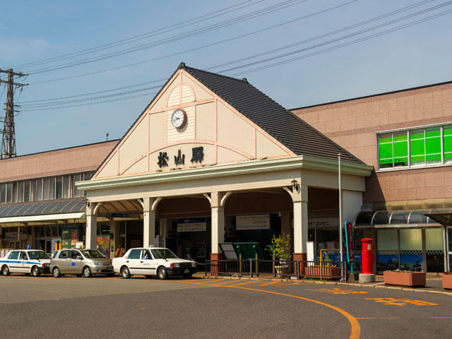 松山駅は愛媛県の県庁所在地・松山市に位置しています。市の中心地からは少し離れているため、落ち着いた雰囲気の駅となっています。駅舎の外観は夏目漱石の小説「坊っちゃん」の舞台となっている中学校や駅をイメージして造られており、駅前のガス灯と共にレトロ感を醸し出しています。構内にはベーカリーや100円ショップ、コンビニや軽食店があり、お土産品を購入することもできます。 松山駅に乗り入れているのはJR四国の予讃線(よさんせん)です。予讃線は高松市の高松駅から瀬戸内海を沿うように愛媛県宇和島駅までを走り、美しい景色を眺めながら列車の旅を楽しめる路線です。また、松山駅前からは路面電車・伊予鉄道が市内を巡っています。道後温泉までの道のりをゆっくりと進んでおり、坊っちゃん列車と呼ばれる蒸気機関車型の車両も運行されています。伊予鉄道の松山市駅と松山駅は異なる駅のため注意が必要です。 国内でも有数の城の「松山城」はウォーキングコースを歩いてみたり、絶景や夜景ポイントなどの見所もあり、ぜひ訪れてほしい観光スポットのひとつです。松山駅改札口方面から車で8分ほどの距離にあります。また、小泉八雲の作品集『怪談』にも収められている「うば桜」の舞台となっている「大宝寺」は、松山駅西側から車で約6分。国宝の本堂は趣があり、心落ち着く場所となっています。 松山空港から松山駅までは県道18号線に乗っておよそ12分と、とても近い距離にあります。