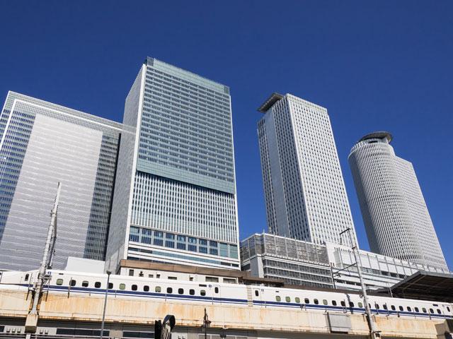 """東京・大阪に続く、日本三大都市のひとつ愛知県名古屋市。その中心にある名古屋駅は、JR東海道本線・新幹線と、名古屋港まで延びる名古屋臨海高速鉄道「あおなみ線」、名古屋市営地下鉄の4つの路線が乗り入れる巨大なジャンクション駅です。「名駅(めいえき)」の愛称でも親しまれ、1日約40万人が利用しています。 駅の周りには、駅ビル「JRセントラルタワーズ」をはじめ、ミッドランドスクエアや、名古屋ルートタワーセンターなど、オフィスと商業施設を兼ね備えた高層ビルが林立しています。名鉄百貨店メンズ館前にある、巨大なナナちゃん人形は、待ち合わせ&フォトスポットとして人気です。飲み物を注文すると、トーストやサラダがついてくる""""名古屋式モーニング""""や、天むすにきしめんなど、名古屋グルメを楽しむなら、国内最大級の広さを誇る名駅地下街を利用しましょう。 """"戦国三英傑""""として名高い、織田信長や豊臣秀吉、徳川家康とゆかりのある名古屋市には、観光スポットも目白押しです。 日本三名城のひとつ「名古屋城」へは、駅から車を利用して約20分、三種の神器のひとつ「草薙の剣」を祀る「熱田神宮」へは、約25分でアクセスできます。遠方へのアクセスには、駅の東側に延びる名古屋市の中心部を東西に貫く幹線道路「錦通り」、または、駅から5分圏内の名古屋高速都心環状線・名駅入り口をご利用ください。"""