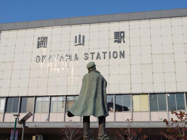 岡山駅は岡山県・岡山市にあり、県の中心となるターミナル駅です。四国・山陰地方への連絡口として、特急列車も多く発着しています。飲み屋街のある方は飲食店が多く集まっていて賑やかである一方、近くには大きな公園もあり、平日の朝や休日には運動している人が数多くいます。新幹線の駅でありながらすぐそばには自然を感じられる環境が広がっています。  また、地下街が充実しているのも岡山駅の特徴。買い物スポットやグルメスポットが点在しているほか、岡山市内の主要な場所と地下を通して結ばれています。雨の日などは濡れることなくアクセスできるので便利です。  駅から行ける観光名所の1つとして「岡山城」があり、黒漆塗りの姿が特徴的です。旭川が城の背後を流れており、川面と黒塗りの城とのコントラストが印象的な風景。宇喜多秀家が秀吉の指導により築城にあたった城であり、豊臣時代を伝える数少ない城として貴重です。  岡山に来た記念としてお参りをしたいなら、北区吉備津にある「吉備津神社」に行ってみましょう。大吉備津彦大神を主に祭っており、山陽道では屈指の大社。大吉備津彦大神は古くからこの地方の開拓の大祖神として尊崇されてきた存在で、桃太郎伝説のモデルになったともいわれています。神社には鬼退治にまつわる神話も残されていて、鬼と恐れられていた一族を退治することができてこの地に平和と秩序がもたらされたのだそうです。  岡山駅の周辺にはレンタカーのお店が複数あるので、歴史と豊かな自然を楽しみにドライブに出かけるのがおすすめです。