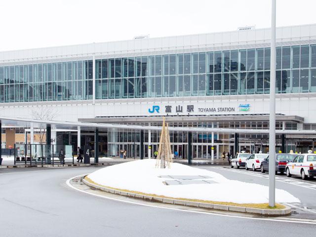 富山駅は、五箇山の合掌造り集落や黒部ダムがある、富山県の玄関口です。2015年に開通した北陸新幹線と、在来線のJR高山本線、あいの風とやま鉄道線が乗り入れています。富山きときと空港(富山空港)から富山駅は、車でおよそ20分です。路面電車の富山地方鉄道(通称・市電)の停留所は、駅の北口と南口にあります。 富山のドライブで注意したいのが、市街を走る路面電車です。道路は原則、路面電車が優先されます。右折や横断のタイミングを除いて、レールのある軌道敷内に立ち入らないようにしましょう。路面電車が右左折する交差点には、車の信号と並んで矢印型、×字型をした市電専用の信号があります。見間違えの無いようご注意ください。 駅周辺は、県庁、市役所やデパートが集まる富山市の中心市街地が広がっています。南口駅前にある「きときと市場とやマルシェ」やCiC(シック)ビル1階の「ととやま」で、富山名物の「ますのすし」をはじめとする特産品や名産品がお土産として購入できます。 市内の主な観光スポットも、駅の周囲に集まっています。北口の富岩運河環水公園と、南口(正面口)の富山城址公園は、それぞれ駅から1km圏内です。山王まつりで有名な日枝神社は、富山城址公園の近くです。6月1日・2日を中心に開催される山王まつりは、富山市の一大イベント。例年20万人以上の人出で賑わいます。 北陸自動車道の富山ICは、駅から国道41号線経由で約20分。新潟方面に12kmほど走れば、立山黒部アルペンルートの最寄りインターとなる立山ICに到着します。