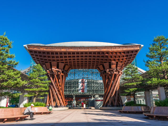 金沢駅は石川県の県庁所在地、金沢市の中心駅です。2015年に開通した北陸新幹線で、東京から約2時間30分でアクセスできるようになりました。在来線は、JR北陸本線とIRいしかわ鉄道線が乗り入れています。 金沢駅は、新幹線開通とあわせて新駅舎になりました。市街中心部に向かう東口は「兼六園口」、県庁や金沢港方面の西口は「金沢港口」と改称されています。兼六園口の入口に設けられた木造の鼓門(つづみもん)と、ガラス製のもてなしドームは、金沢の新しい名所です。北陸鉄道の北鉄金沢駅は、もてなしドームの地下にあります。 金沢観光の定番、兼六園と金沢城は、金沢の中心市街地で隣接しています。金沢駅から兼六園までの距離は、およそ2.5kmです。鼓門から伸びる金沢駅通りから、近江町市場近くにある武蔵交差点を直進すると、金沢市街の主要な観光スポットにアクセスする百万石通りに到着します。ひがし茶屋街と主計町茶屋街の近くにある橋場交差点は、武蔵交差点を車で直進、およそ3分です。兼六園や金沢城公園に直接向かう場合は、武蔵交差点を右折してから、東急ハンズに面した香林坊交差点を目指しましょう。北陸地方のドライブで便利な北陸自動車道の金沢東ICは、駅から車で約15分。金沢森本ICは約20分です。 毎年6月の第1金、土、日曜日に開かれる金沢百万石まつりは、金沢市の一大イベントです。期間中は、駅から兼六園にかけての広い区間で交通規制が行われます。当日は、周辺の臨時駐車場に車をとめてから、会場までバスで移動するパーク&ライドも利用できます。お出かけの際は、金沢百万石まつり実行委員会のHPで実施状況を確認しましょう。