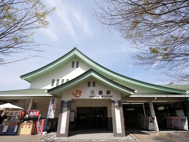 """東京から新幹線を利用して約1時間。静岡県三島市の中心にあるJR三島駅は、首都圏の奥座敷として名高い伊豆半島の玄関口です。東海道本線・新幹線とともに、半島中央部へと延びる伊豆箱根鉄道駿豆線が乗り入れ、伊豆観光のアクセス拠点として活躍しています。駅南口に併設された三島市観光案内所では、市内外にある観光スポットの最新情報を入手することも可能です。 約1万年前に噴火したとされる日本最高峰の富士山。その溶岩流の末端で形成された三島駅周辺は、富士山から流れる湧き水が豊富な「水の都」としても知られています。駅の周りには、豊かな水がもたらした自然林が美しい市立公園「楽寿園」や、夏の夜にはホタルが飛び交い、幻想的な景色を楽しめる源兵衛川など、自然を体感できるスポットが目白押しです。天然水で臭みを取り除いた名物「三島うなぎ」や、しっとりとした食感が特徴の三島馬鈴薯(メークイン)を使用した「三島コロッケ」は、市内各地にあるカフェやレストランで味わえます。 三島駅の改札口は、北口・南口の2ヵ所。双方の直通の連絡路はないため、間違って反対側に出てしまった場合には、通り抜けようの""""入場券""""を購入するか、または遠回りをする必要があります。お出かけ前に、利用する出口をしっかり確認しておきましょう。 人気の観光スポット「三島スカイウォーク」や、""""日本一深い海""""駿河湾に面する「沼津港深海水族館」へは、三島駅から車を利用して約30分でアクセスできます。"""