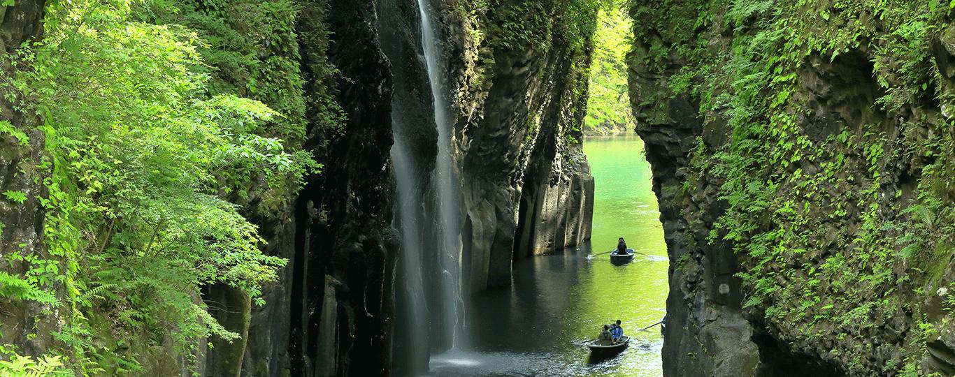 宮崎県は、年間の平均気温が約17度という温暖な気候が特徴で、太平洋に面した美しいビーチや豊かな自然に囲まれています。南国ムードが漂っており、ハネムーンの聖地としても人気です。 市街地から車で約20分のリゾート施設「フェニックス・シーガイア・リゾート」は国内外から多くの観光客が訪れます。広大な敷地内にはゴルフ施設「フェニックスカントリークラブ」や43階建ての高層ホテル「シェラトン・グランデ・オーシャンリゾート」などがあり、スポーツやスパ、温泉などを楽しむことができます。 宮崎市の中心部から車で約30分ほどの場所にある青島エリアも有名な観光スポットです。海水浴やサーフスポットとして有名な「青島ビーチ」の「弥生橋」を渡ると、「青島」という周囲1.5kmほどの小さな島があります。島の周りは「鬼の洗濯岩」という波状の岩に囲まれており、島の中には「青島神社」という縁結びで有名な神社があります。 青島エリアから更に南下すると、イースター島から許可を受けて復刻したモアイ像が並ぶ「サンメッセ日南」があります。同じ日南市内にある「飫肥城跡(おびじょうあと)」とその城下町は重要伝統的建造物群保存地区にも指定されており、風情ある街並みの中で食べ歩きなどを楽しめます。 宮崎市から車で約2時間、宮崎県最北端の高千穂町も観光地として有名です。五ヶ瀬川の流れでできた大渓谷「高千穂峡」は絶景スポットで、多くの神話も残されています。緑と断崖に囲まれた遊歩道を歩いたり、渓流をボートで往復して「真名井の滝(まないのたき)」という大きな滝を間近で見たりと大自然を存分に味わえるスポットです。