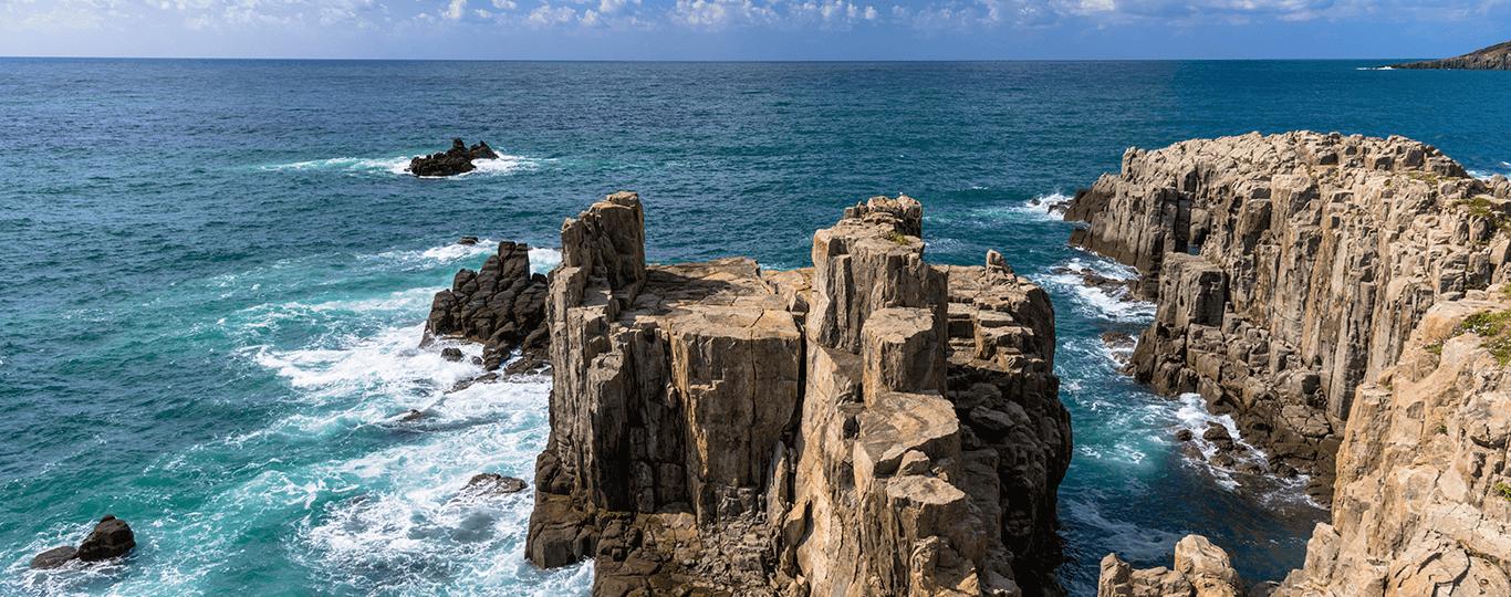 福井県は北陸地方の最南端に位置し、若狭湾と日本海に面している県です。若狭湾は京都の丹後半島から福井の越前岬の間の湾で、リアス式海岸が続いています。若狭湾の絶景を望めるスポットが、「レインボーライン山頂公園」です。標高400mの梅丈岳の山頂にある公園で、三方五湖有料道路(レインボーライン)の中間地点に位置しています。ケーブルカーやリフトで山頂に上ると、三方五湖や若狭湾を一望する360度のパノラマを楽しめます。「東尋坊」は福井を代表する景勝地で、柱状節理によって形成された断崖絶壁がおよそ1kmにわたって続く海岸です。陸地からでも大迫力の景観を楽しめますが、遊覧船で廻ると、さまざまな形状の柱状節理を見ることができます。 福井県勝山市は恐竜の化石発掘が盛んな街です。「福井県立恐竜博物館」では、福井をはじめ国内で発見された44体の全身骨格を展示しており、そのうち11体は実物です。また、巨大スクリーンに映し出されるCG映像やジオラマで、太古の世界を体験できます。 勝山市から西に車で40分ほど走ると、「永平寺」にアクセスできます。永平寺は、1244年に曹洞宗の高祖・道元禅師が禅修行の道場として開山しました。現在でも200人以上の修行僧たちが厳しい修行を行っている禅寺です。33万㎡の境内には樹齢700年を超える杉の木が生い茂り、荘厳な雰囲気を醸し出しています。道場の中心である七堂伽藍の見学の他、座禅や写経も体験できます。