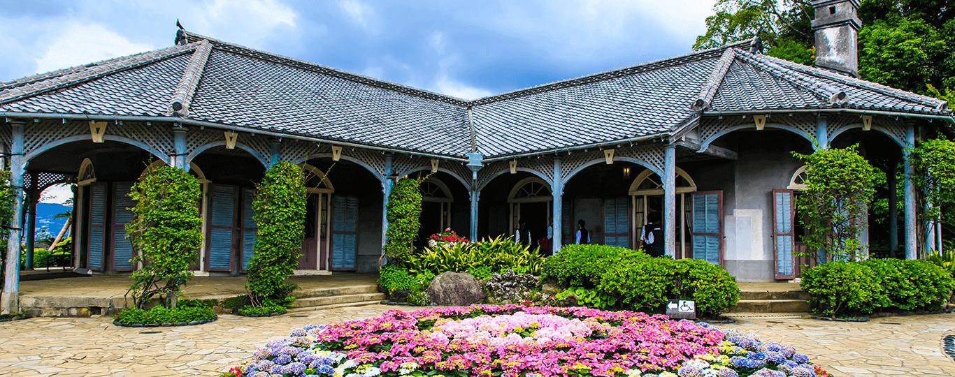 長崎県は大陸や西洋と日本が入り交じった独特の文化を感じられる観光スポットが多い県です。「出島(でじま)」は鎖国時代に日本の中で唯一西洋との貿易のために開かれていた人工島で、ここから長崎県に外国のさまざまな文化が入ってきました。現在の出島は江戸?明治時代の建物が復元されており、当時の雰囲気を味わえます。 長崎市内の「グラバー園」は明治時代に長崎にあった洋館を移築・復元しており、長崎港や稲佐山の景色を楽しむことができます。「大浦天主堂(おおうらてんしゅどう)」は幕末に日本が開国したとき在留外国人のために建てられた、国内に現存する最古のゴシック調の協会堂です。「長崎と天草地方の潜伏キリシタン関連遺産」として世界遺産に登録された遺産郡の一つにもなっており、キリスト教が弾圧された時代の潜伏キリシタンの歴史について学ぶことができます。 「眼鏡橋」は1634年につくられた日本初のアーチ式石橋で、国の重要文化財にも指定されています。日本日本三大中華街のひとつである「長崎新地中華街」には中華料理店や雑貨店などが並び、食べ歩きなどを楽しめます。他にも長崎市内には「平和公園」「長崎原爆資料館」など長崎に落とされた原爆や平和について学べるスポットもあります。 佐世保市のテーマパーク「ハウステンボス」は長崎市内から車で約1時間15分です。パーク内はヨーロッパの街並みが再現されており、美しい花やイルミネーションやショーが楽しめます。