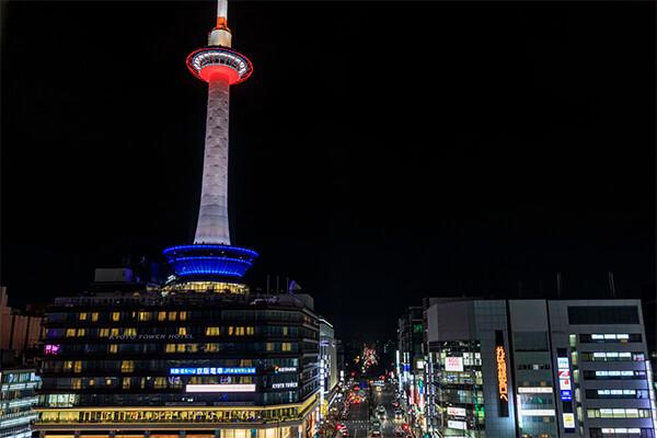 「京都タワー」は京都駅前のバスターミナルを挟んで向かいに建つ、京都のシンボルタワーです。もともと京都中央郵便局があった場所に1年10カ月の月日をかけて建築され、1964年から営業が始まりました。すでに建築から50年を超えていますが、産業や文化、観光の拠点、そして京都の玄関口としての役割を担う存在であり続けています。京都タワーは鉄骨を全く使わない構造で、真っ白な円筒形のフォルムが特徴的です。高さ約100mの場所には展望台があり、タワーの下は地下3階、地上9階のビルになっています。 展望台からは360度見わたすことが可能です。京都の有名スポットを上から眺められるのはもちろん、夕暮れ時や夜景が美しいスポットでもあります。タワー下の建物内にはレストランやスカイラウンジがあるほか、地下3階は一息つくことができる大浴場になっています。さらに、地下1階から地上2階に「KYOTO TOWER SANDO(京都タワーサンド)」が2017年4月にオープンしました。地下1階は和洋中のレストランからスイーツのお店まで多彩な飲食店が入るフードホール、1階は京都ならではのアイテムも購入することができるマーケットのフロアです。2階はワークショップのフロアで、和菓子作りや伝統工芸などさまざまな体験ができます。 京都駅からは地上を歩いて約2分で京都タワーまで行くことができますが、地下通路を通って直接アクセスすることもできるため、天気の悪い日でも訪れるのに困りません。5階から9階までは「京都タワーホテル」になっており、京都に宿泊する際にも便利です。