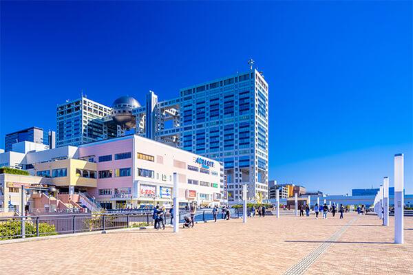 「お台場」は東京湾に浮かぶ埋立地で、広くは東京臨海副都心を含む一帯のエリアを指します。その歴史は古く、1853年にペリーが来航したことに危機感を持った江戸幕府が、砲台となる6つの台場を建設。現在はそのなかのひとつが公園として、もうひとつは史跡として残った形となりました。 公園は「お台場海浜公園&台場公園」の名で、カップルや家族連れで賑わうお台場の観光スポットとして広く親しまれています。公園内で特に人気のビュースポットからは「レインボーブリッジ」のパノラマ風景を眺めることができ、夜のライトアップでは3色に光るイルミネーションを夏と冬で違うバージョンが楽しめます。春から秋にかけては約800mの長さの人口ビーチにてさまざまなイベントが開催され、周辺の地域にはマリンスポーツや釣りができるエリアもあります。レジャーランドの要素が多いお台場ですが、一方では高台に砲台跡や火薬粉跡などの史跡が残されており、お台場の歴史を辿ることもできます。 お台場エリアのシンボル「フジテレビ本社ビル」の周辺には、ショッピングやグルメスポットとして名高い大型のショッピングモールが並び、また温泉や車のテーマパークもあります。いずれも訪日観光客が気軽に立ち寄れるスポットとして人気を博しています。車でお台場のショッピングエリアまで行かれる場合、首都高速11号台場線の台場出口からおよそ3分、羽田・横浜方面から高速湾岸線を利用する際は臨海副都心出口から約1分、千葉方面からは有明出口より5分ほどの距離になります。