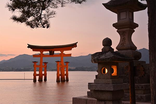宮島は、広島湾の西の方に位置する島で、最も近い所で本州から500mほどの距離です。宮島へは宮島口桟橋からフェリーに乗って10分ほどで到着します。宮島は正式には「嚴島」という島ですが、お宮のある島ということから宮島と呼ばれるようになったと言われています。人々は古代より宮島を神として崇拝していました。「嚴島神社」となったのが593年。安芸国の豪族であった佐伯鞍職(さえきくらもと)によって神社として創建されました。神社が陸地ではなく海上に建てられたのは、島全体を神そのものと捉えていたためです。 嚴島神社は、本殿と客(まろうど)神社、平舞台、能楽屋などが回廊でつながれた寝殿造りの様式で建てられています。現在の社殿の姿になったのは1146年。安芸守となった平清盛が極楽浄土をイメージし、瀬戸内海を池に見立てて造営したと言われています。海や「弥山(みせん)」の原生林を借景とし、朱塗の鳥居や社殿が見事に自然と調和した美しい姿が称えられ、1996年にユネスコの世界文化遺産に登録されました。 宮島とともに世界文化遺産に登録された弥山は、弘法大使が806年に開基した山です。長くご神体として崇められてきたため今でも原生林が残り、花崗岩の地質であることから風化して不思議な形になった奇岩怪石が多く見られます。また、由緒ある古刹や七不思議と呼ばれる伝説も残されており、パワースポットとして人気である他、山頂からの景色も楽しめます。山上までの所要時間は、宮島ロープウエーで15分ほどです。