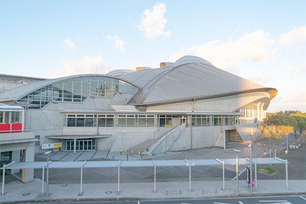 「幕張メッセ」は、東京駅から最速で約23分ほどでアクセスが可能な、複合コンベンション施設です。1989年に千葉県千葉市美浜区に開業し、その敷地面積は約21万m2ほど。エリア内は「国際展示場」と「国際会議場」「幕張イベントホール」の3施設に分かれおり、それぞれ全天候対応の施設では用途に合わせた様々なイベントで使用されることが特徴です。 国際展示場は、赤い屋根が目印の1-8ホールと海浜幕張駅からのアクセスに便利な9-11ホールの2つの建物に分かれ、大きな見本市や展示会、音楽イベントのコンサートに使用されています。国際会議場は、1600名の収容が可能なコンベンションルームと大小合わせた22の会議室があり、セミナーや講演会が開かれ、企業研修の場としても利用が可能です。また、ドーム型でアリーナ形式の幕張イベントホールは、最大で9000名の収容が可能で、式典やコンサートに使用されます。様々な室内スポーツのコートにも対応していることから、スポーツイベントも頻繁に行われます。なお、座席や入場口などは、イベント等により異なるため、チケットをよく確認することが必要です。 施設内の各所には、ATMやコインロッカーの設置があり、有料駐車場も利用できます。また、授乳室の完備、おむつ交換台の設置があるので、小さなお子様連れの方にとっても便利です。車椅子の無料貸し出しや身障者用トイレ、オストメイトの設置などバリアフリーにも対応しています。