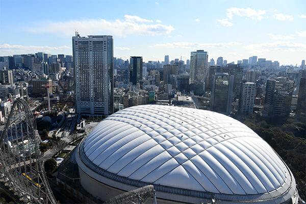 1988年に開業した「東京ドーム」は、東京都文京区に位置する、全天候に対応可能なドーム型の多目的スタジアムです。温浴施設やレストラン、アミューズメント施設が集まる、東京ドームシティの中心となる施設としても知られています。日本プロ野球の球団が専用球場として使用しており、公式戦が開催されていることから、野球観戦をすることが可能です。また、最大収容人数が55000人の巨大スタジアムなので、格闘技やコンサート、展示会等も開催されており、年間を通じ様々なイベントに利用されています。 東京ドーム内には、お弁当や飲み物を販売する売店があり、観戦等をしながら飲食をすることが可能です。また、お土産ショップでは限定アイテムなどの取り扱いがあり、訪れた記念のグッズを買うこともできます。入場の際は、イベント等により座席や入場ゲートが異なるので、チケットを確認してから係員の指示を仰いでください。さらに、東京ドームでは、事前予約の見学ツアーも随時開催中です。普段はなかなか訪れることができないバックヤードの見学や記念撮影ができる貴重な機会となります。 電車でのアクセスは、JR線または都営地下鉄三田線「水道橋駅」の利用が便利です。東京メトロ丸ノ内線・南北線「後楽園駅」や都営地下鉄大江戸線「春日駅」からもアクセスが可能。車やバイクで向かう場合は、有料の駐車場を利用することができます。指定の施設や店舗の利用で時間割引を受けることができるため、店員やチケットカウンターの係員にお問い合わせください。