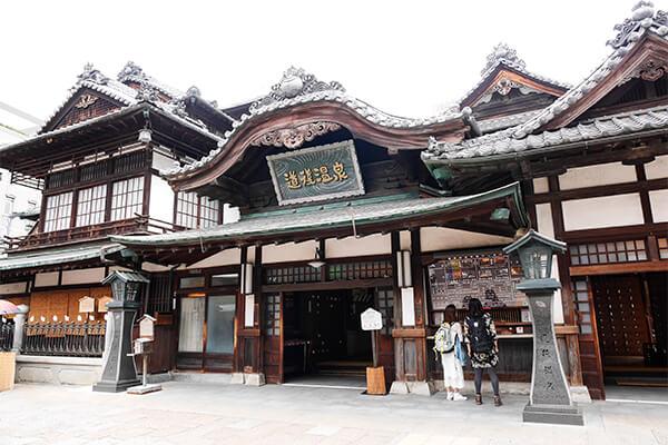 「日本書紀」にもその名が残る日本最古の温泉といわれる愛媛県松山市の「道後温泉」。古典作品や夏目漱石の坊ちゃんにも登場する日本有数の温泉地です。その中でも有名な「道後温泉本館」は、1894年初代湯の町町長の伊佐庭如矢氏が、「100年後にも他がまねできないものを」と銘打って改築したもの。3階三層楼(さんそうろう)の振鷺閣の窓は、夜になると明るく光ります。1日3回打ち鳴らされる時刻を告げる太鼓の音は、「残された日本の音風景100選」に定められています。 道後温泉の泉質は刺激の少ないアルカリ性単純泉で、日本人の肌に合い、湯治の他美容にも適していることから「美人の湯」ともいわれています。18ある温度の違う源泉がブレンドされ、約42度の適温が維持されている、国内でも珍しい無加温・無加水の源泉かけ流し温泉です。 道後温泉には神湯といわれる本館の他に、飛鳥時代に用いられた建築様式から着想を得た2017年オープンの新湯「別館飛鳥乃湯泉」、蔵屋敷風の造りとなっている地元民が利用する親湯「椿の湯」があり、どれも趣きのある建物で風情を作り出しています。南にある「冠山」の空の散歩道から見下ろせば、道後温泉本館と周囲が一望できます。とくに幻想的な雰囲気のあるここから見る夜景はおすすめです。 道後温泉へのアクセスは、松山空港から車で約30分、JR松山駅からは約25分、市内電車を利用しても時間は変わりません。市営駐車場が2か所、観光駐車場が1か所近隣にあります。