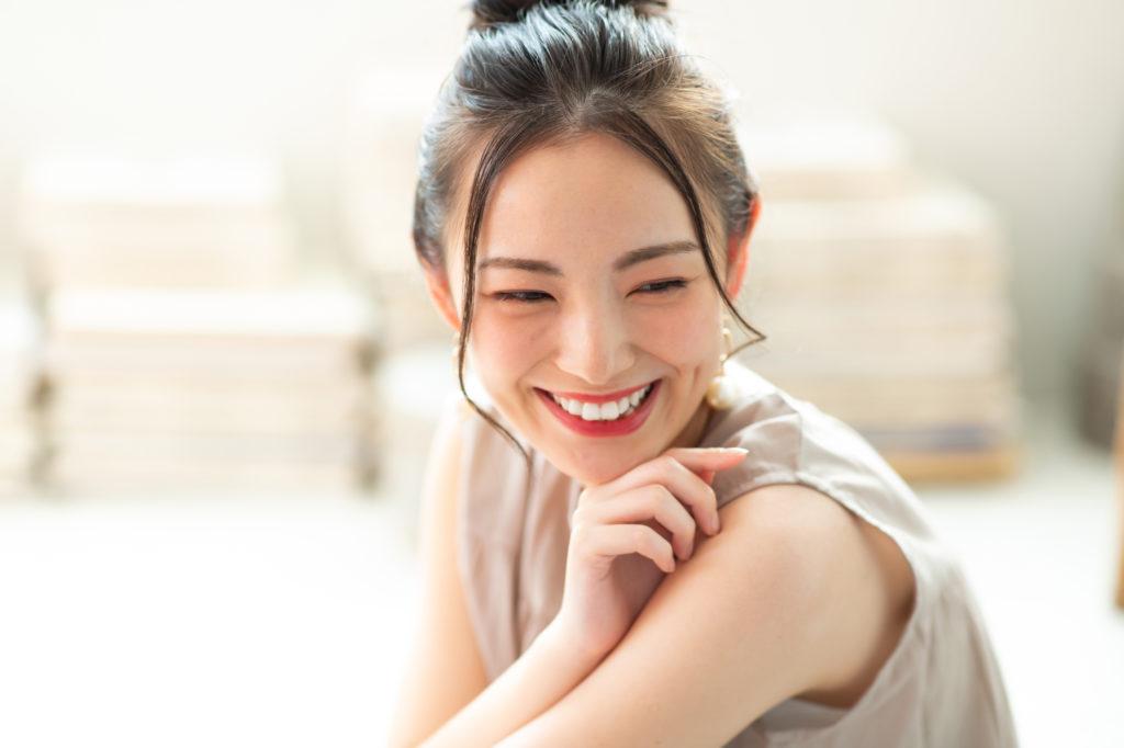 イヤリングをつけて笑う女性