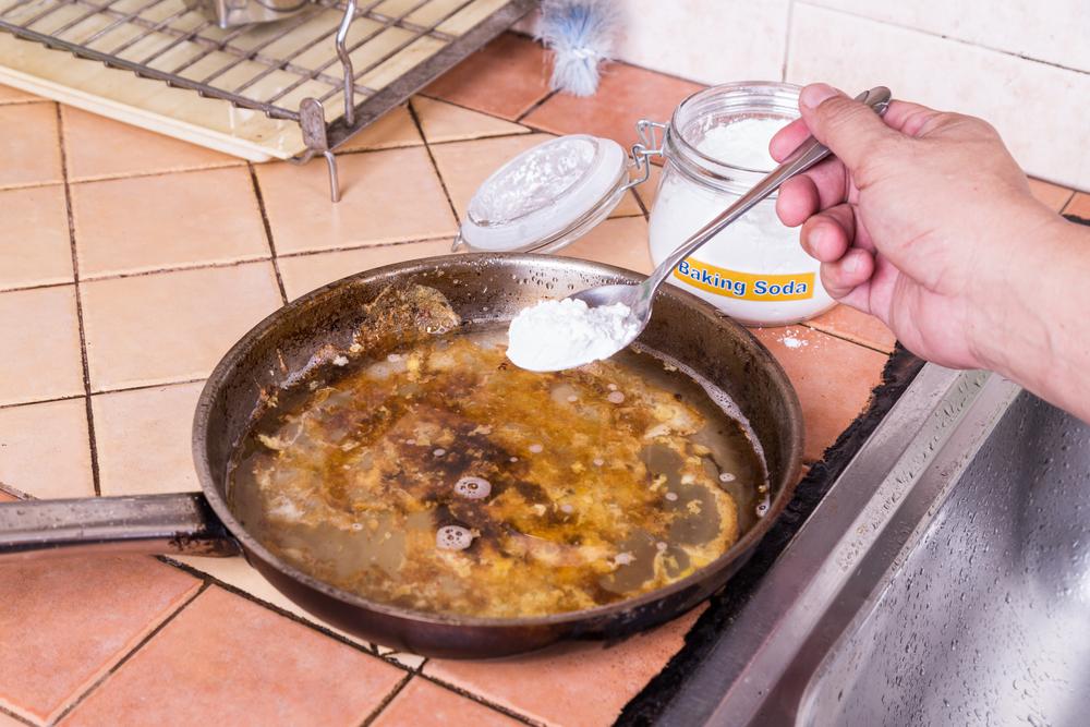 鍋の焦げ付きを重曹で掃除している女性