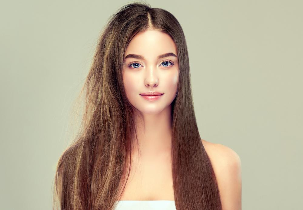 段カットにして髪の毛のクセが出ている女性