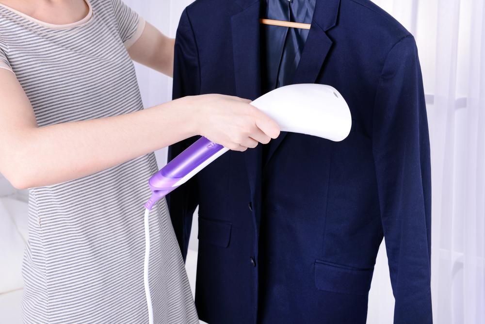 スーツにアイロンをかけている女性
