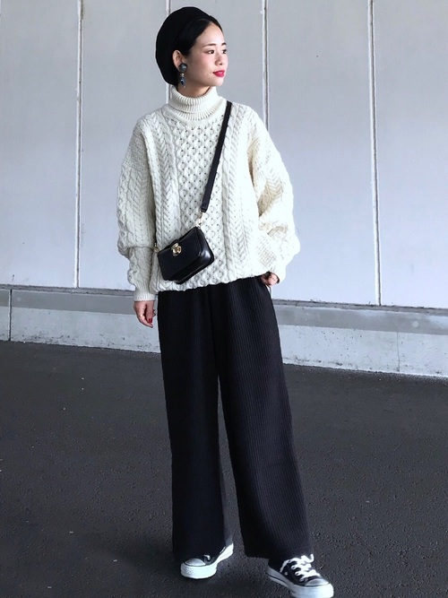 白のアラン編みセーターとニットパンツのコーデ