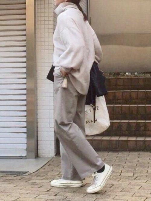 オフホワイトのセーターとライトグレーのパンツのコーデ