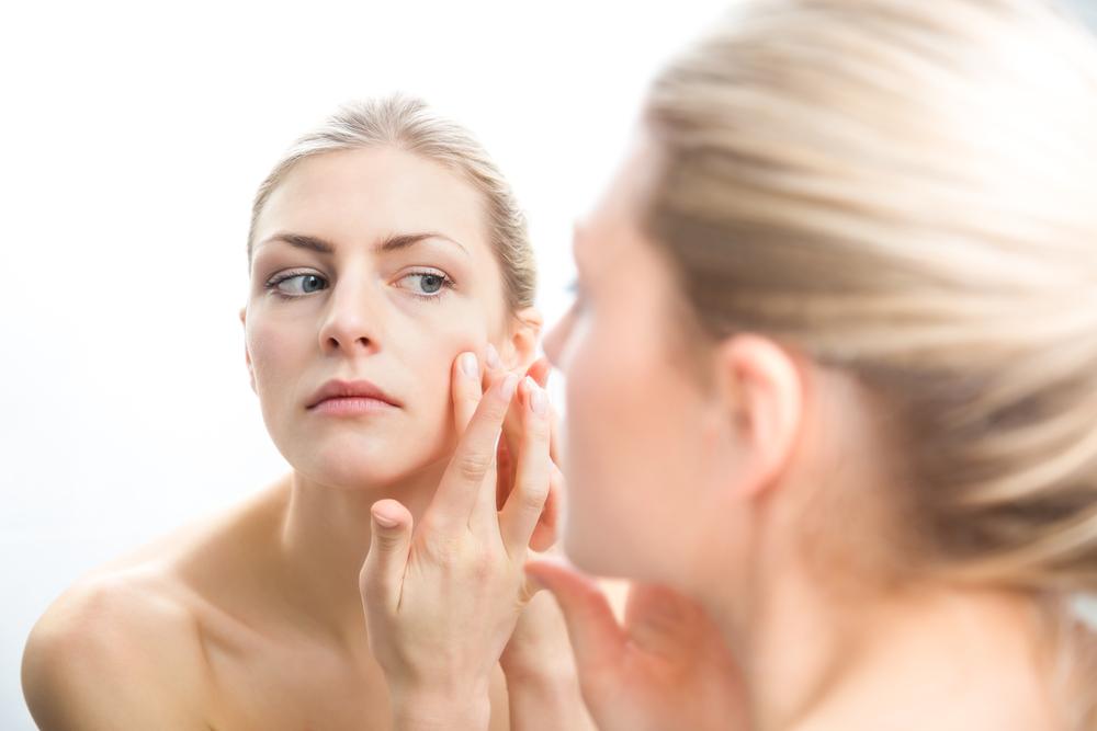 顔を鏡で見ている女性