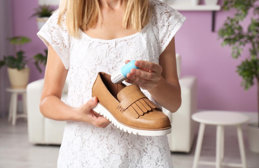 靴に消臭カプセルを入れる女性