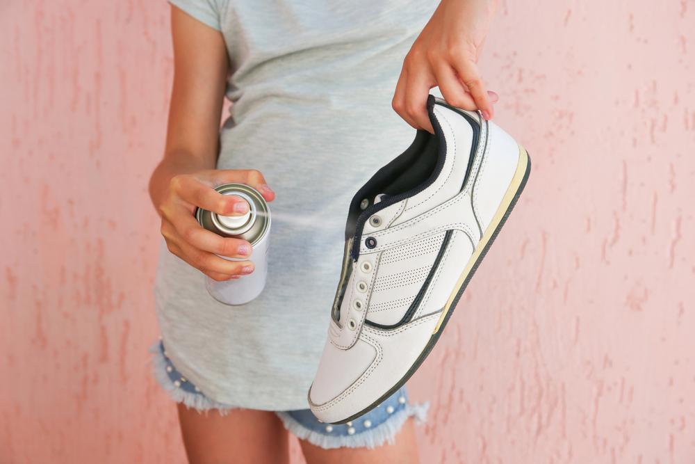 スニーカーに消臭スプレーをする女性