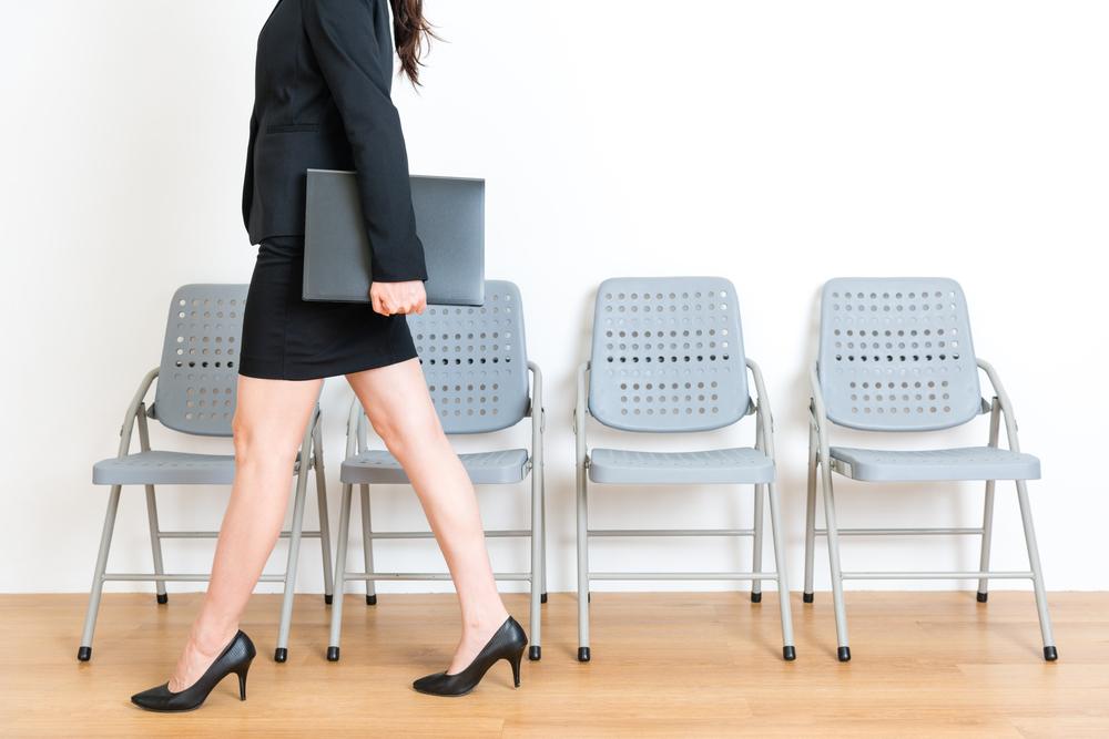 椅子の前を歩いているスーツの女性