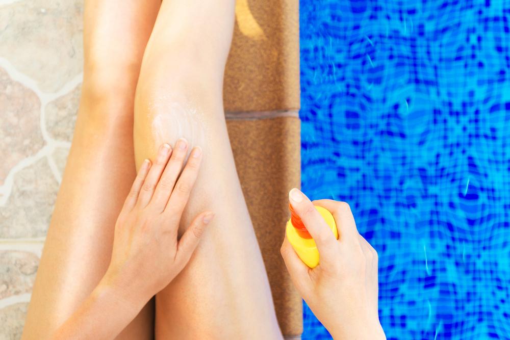足に日焼け止めローションを塗る女性