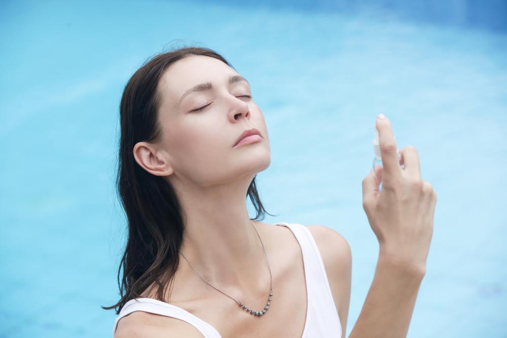 エアコンで乾燥した肌に化粧水をスプレーしている女性