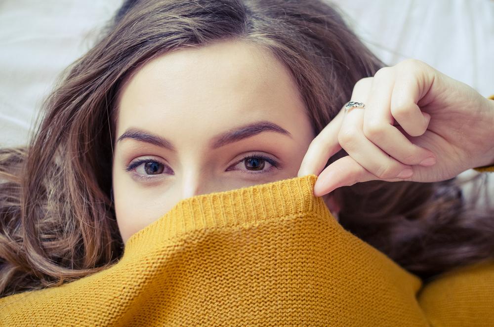 ニットで顔を隠す女性